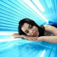 Young woman undergoing tanning skin treatment in solarium
