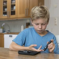 Child with diabetes measuring glucose or blood level in a kitchen