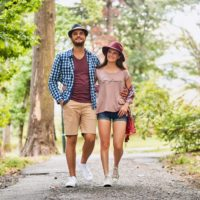 Young couple walking on pathway through grass field